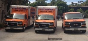 Water Damage Restoration Van And Trucks At Commerical Job Location